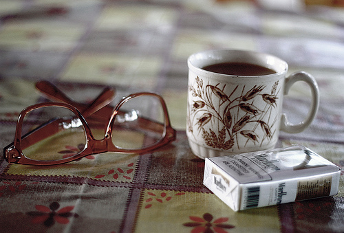 Photo of eye glasses, a cup of coffee and a pack of cigarettes.