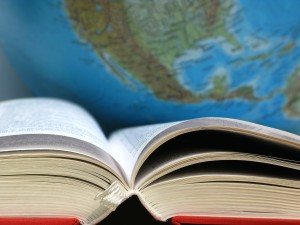 Close up shot of an open, hardback book in front of a globe.
