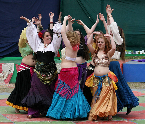 Eight women in brightly colored skirts and tops belly dance in a circle at a Ren fair in Anchorage, Alaska