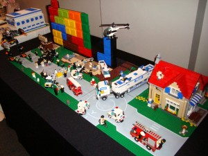 a city scene made out of legos with a giant robot attacking and police trying to stop it