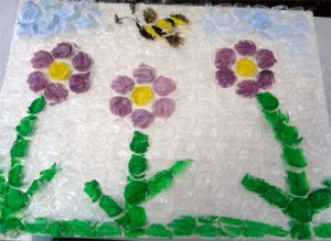 Picture of purple flowers and a bumble bee all made of bubble wrap