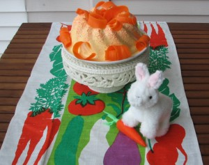 Foreground: plush toy bunny sits with a carrot; Background: Carrot gelatin salad sits on a cake stand.