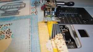 Hemmed fabric being sewn on sewing machine