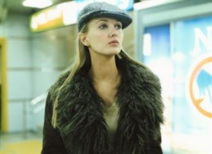Stylish blond woman wearing a tweed hat