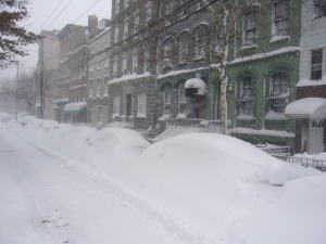 Image of a snow covered city street on a gray, cloudy day.