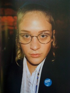 Chloe Sevigny, celebrity actress and fashion designer, is looking straight at the camera, wearing round-lens glasses, a white collared shirt and a black jacket.