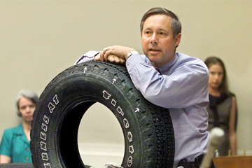 Representative Fred Upton stands with both arms crossed on top of a black Firestone tire.