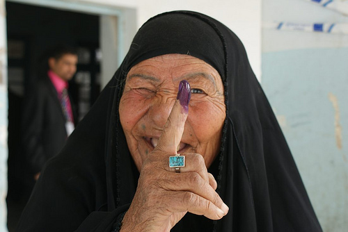 An Iraqi woman smiles and winks after voting in the city of Nasiriyah.