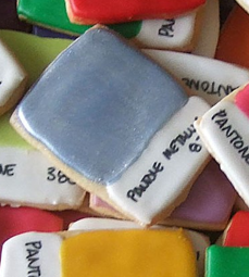Iced sugar cookies made to look like Pantone color chips in a pile, close up view.