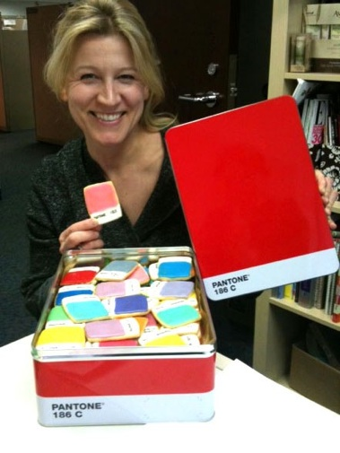 Author Kim is wearing a huge grin as she holds up a pink Pantone chip cookie from a tin filled with cookies.