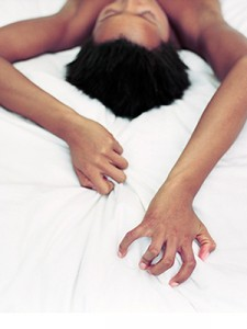 Picture of a woman's head and hands clutching the sheets during an orgasm
