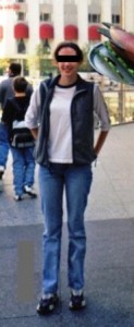 Girl standing in jeans and a long-sleeved shirt and vest