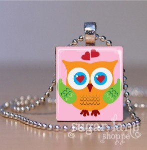 Pink necklace pendant with orange cartoon owl and hearts.