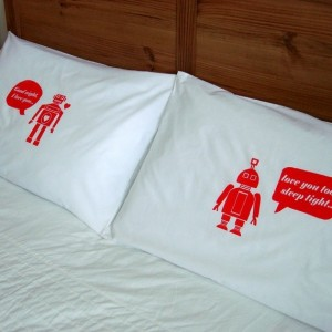 Two pillowcases with a red male robot on one and a red female robot on the other, saying goodnight to each other