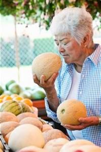 Woman sniffs a melon for freshness