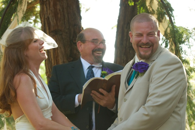photo of bride and groom and officiant laughing