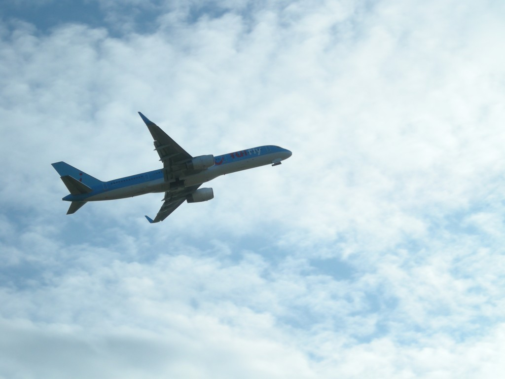picture of an airplane silhouetted against a blue sky with high clouds