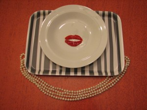 Lips made of pimento on a white plate, surrounded by pearl necklace.