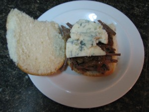 sandwich with layers of pulled beef, caramelized onions, and gorgonzola cheese