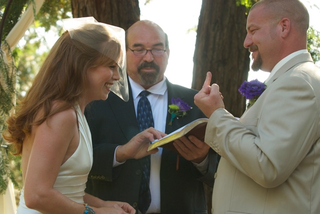 photo of a bride, groom and officiant where the groom looks like he is flipping off the bride but is really showing off his ring finger. The bride is laughing.