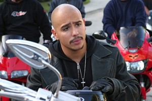 Francis Capra as Weevil on Veronica Mars, wearing a leather jacket and sitting on a motorcycle