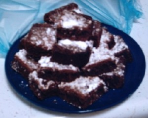 a plate of brownies with powdered sugar on top