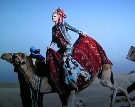 Molly models atop a camel.