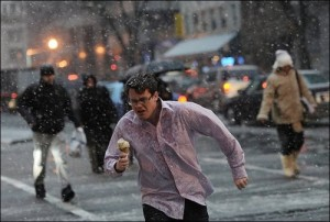White man with brown hair and glasses, running in a snow storm with no jacket, holding an ice cream cone