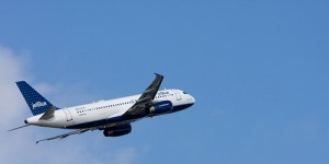 a Jet Blue plane flying across a blue sky