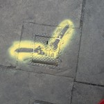 A drain with two spraypainted yellow spanners on it, indicating it has been checked and sealed