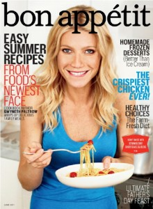 the cover of bon appetit magazine with gwenyth paltrow in a blue top biting her lip holding a plate of spaghetti