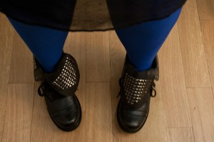 woman wearing bright blue tights and black boots