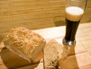 a loaf of bread with the end sliced off and a glass of dark beer next to it