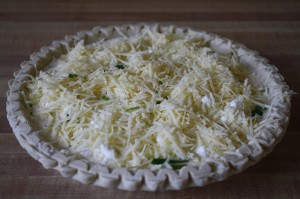 picture of an unbaked pie crust full of cheese, leeks, and other ingredients