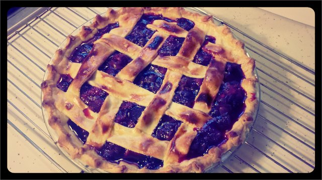 a cherry pie with a lattice crust. the picture has a yellowish filter on it to make it look as if it's from the 1980s.