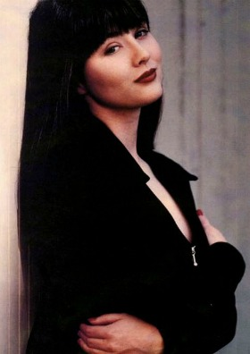 Brenda Walsh leans against a wall, wearing a black top unzipped into a low V. She has one arm across her chest. Her hair is cut into bangs, and she wears a lot of make-up, including red lipstick on her smirking mouth.
