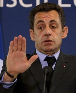 president nicolas sarkozy with an anxious look on his face holding up his right hand, palm facing out as if saying stop