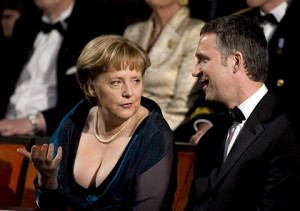 chancellor angela merkel wearing a very low cut black dress speaking with a man with short black hair who's wearing a tuxedo, and she's giving him a serious side-eye look