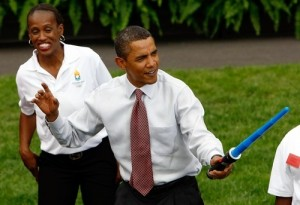 president obama wearing a shirt and tie holding out a blue lightsaber like he is about to duel someone while a woman stands in the background laughing