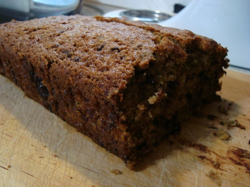 A picture of a large loaf of zucchini bread with chocolate chips, taken from the side. The bread has already been sliced.