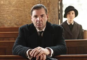 Mr Bates and Anna sit apart in a church