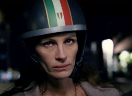 Close-up of Julia Roberts wearing a motorcycle helmet with an Italian flag motif. Her expression is pinched, bored, and contemptuous, all at once.