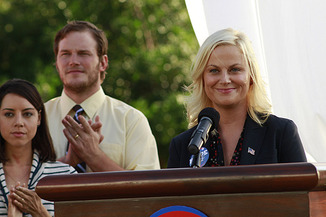 Amy Poehler as Leslie Knope of Parks and Recreation standing behind a podium while two of her coworkers look on clapping