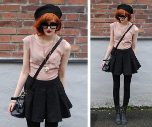 A chic redhead in black tights, a black skirt, black boots and a pale pink top with half-moon tinted sunglasses.