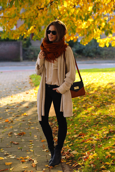 A brunette woman wearing a cream-colored sweater over a cream silk blouse, black jeans and black boots, with a rust brown scarf coiled around her neck.