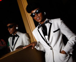 Janelle Monae in a white blazer trimmed with black, wearing black sunglasses, standing next to a mirror.