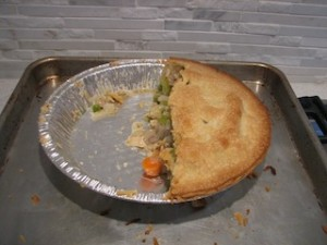Half of a completed turkey pot pie. The other half has already been eaten.