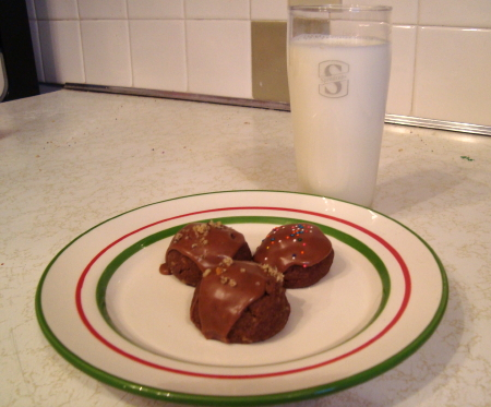 on a small white plate with red and green stripes sit three small, round chocolate cookies. two have nuts, and one has rainbow sprinkles. the plate is accompanied by a glass of milk.