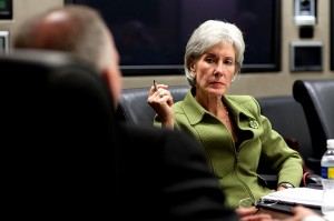 photo of kathleen sebilius - an older white woman with short white and grey hair wearing a green suit jacket. she is holding a pen in her right hand. you can see the back of a man's head in the foreground. Photo taken 4-28-09 by Pete Souza.