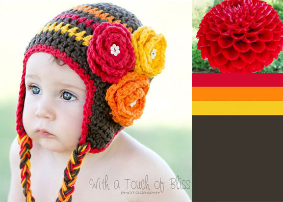 Baby in a knit hat with orange, yellow and pink flowers.